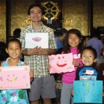 Dharma School children holding smile art