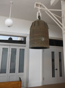 large bell hanging from a bracket outside the hondo