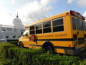 "Small school bus with ""Pacific Buddhist Academy"" on the side, temple in the backround"