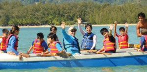 young scouts and adults in an outrigger canoe
