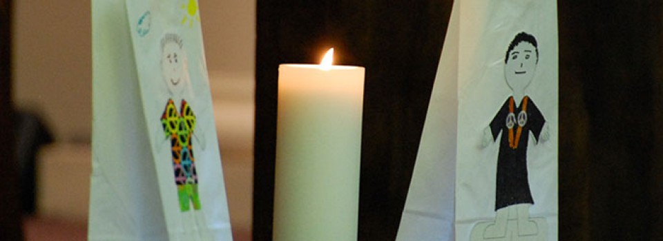 candle with paper sacks on either side featuring figures adorned with peace symbols