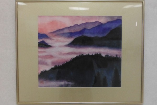 A framed painting of mountains, low clouds, and forest featuring pink and purple sky