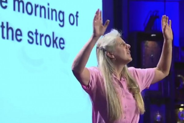 "woman holds up both arms with a projected slide with the words ""morning of the stroke"" behind her"