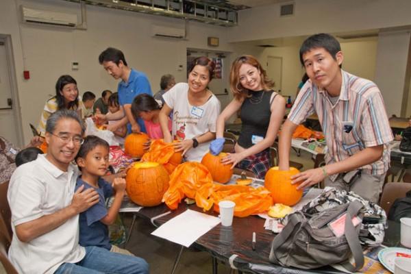 participants carve pumpkins in the social hall