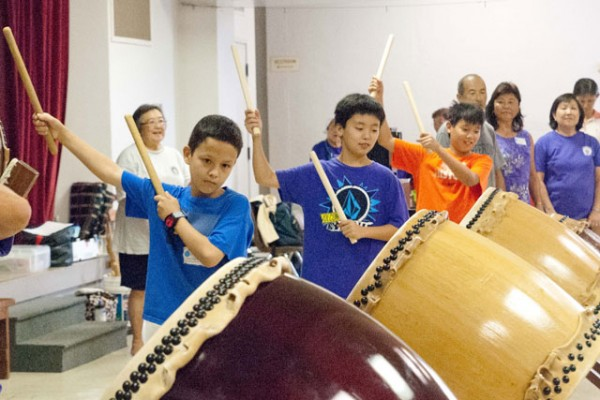 boys playing taiko drums in the social hall