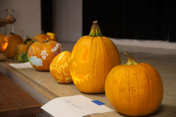 carved pumkins lined up on the stage in the social hall