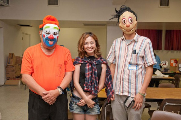 ministers in clown masks on either side of a visitor from Japan