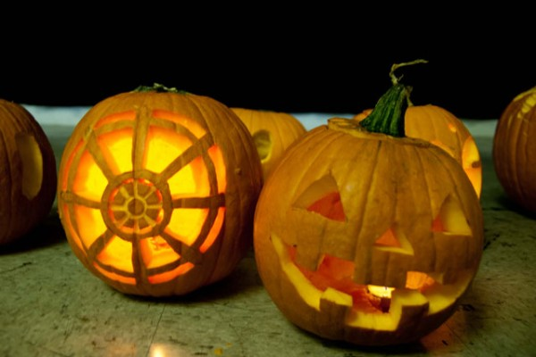 two jack-o-lanterns, one traditional and one with a Dharma wheel design