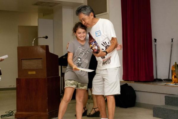 event organizer congratulates girl participant at Pumkins, Dharma, and Fun