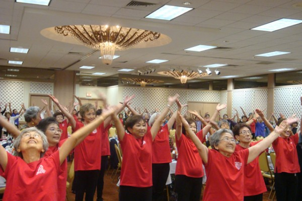dancers with red t-shirts and upraised arms in a ballroom