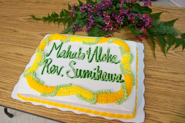 "A cake decorated with a lei and the words, ""Mahalo & Aloha Rev. Sumikawa"""