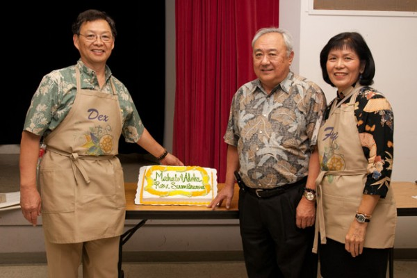 "Reverend Sumikawa with Dexter and Faye Mar. A cake on the table is decorated with the words, ""Mahalo & Aloha Rev. Sumikawa"""