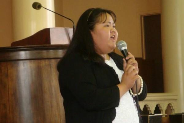 Brandi Yamamoto sings, holding microphone