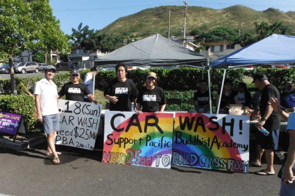 colorful car wash sign held by ministers and youth with PBA cafe tents