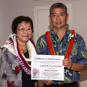 a woman and a man wearing lei holding an award certificate