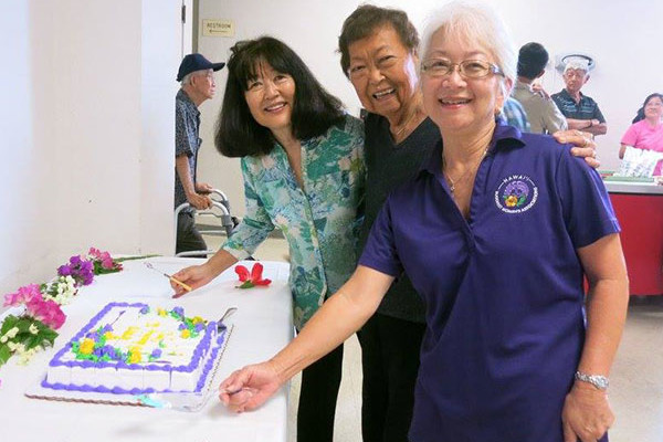 three women show off a sheet cake