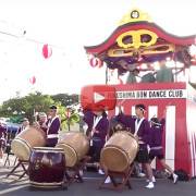 Betsuin taiko group in front of the yagura with video play button overlaid