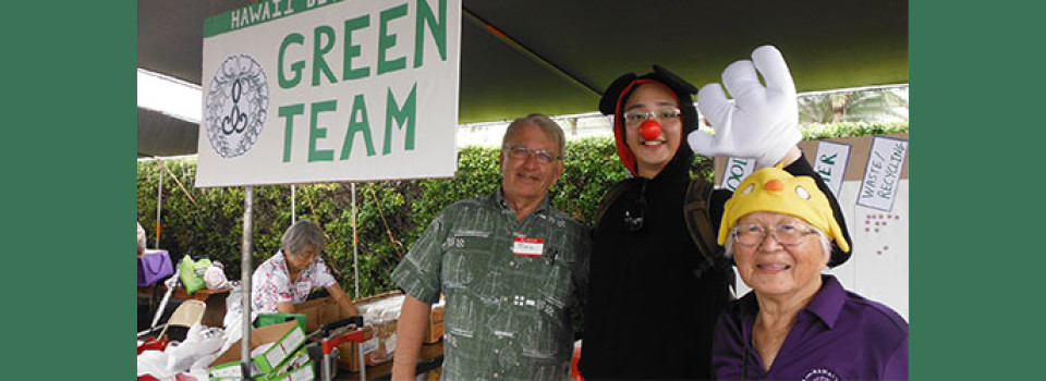 Green Team sign with team members, including Rev. Tomioka with Disney-esque costume