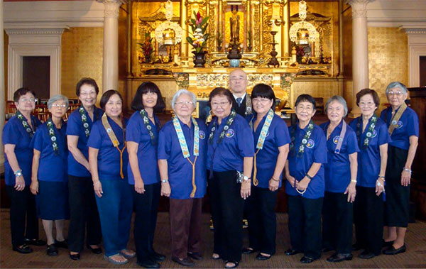 women in purple shirts in front of the altar in the hondo