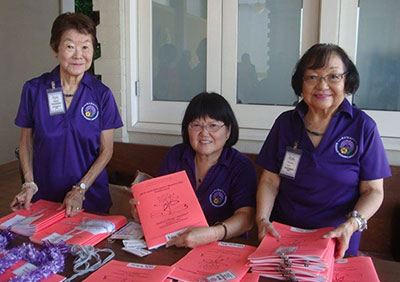 three women with red program books at a registration table