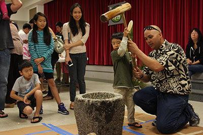 young boy pounds rice with a big mallet with adult helping and other students looking on