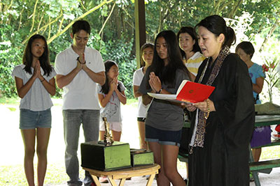 Rev. Hasebe in robes reading from the red service book with children and adults in an outdoor setting
