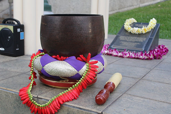 iron bowl gong sits on pad with lei