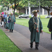 ministers in green robes lead a line of walkers into Honolulu Hale Civic Grounds