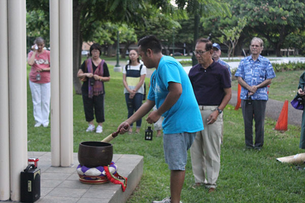 man in blue t-shirt reaches down to gently strike a bowl-shaped gong