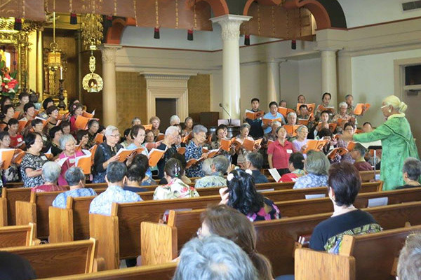 choir members in front of Hawaii Betsuin altar singing with orange song books, Nola Nahulu directing