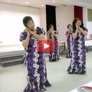 women in purple and white dresses performing hula in the social hall