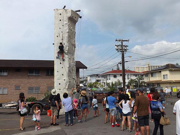 An approx. 25-foot rock climbing pillar at the HMS Fun Fair with a climber half way up and a crowd at the base