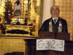 Rimban Hagio uses a visual aid, 6x3x2x3, while giving the New Year's Eve dharma message