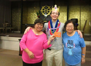 """Rev. Tomioka in """"crown"""" and lei with two party attendees"""