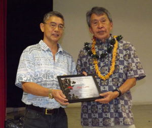 two men holding a framed certificate, one wearing lei
