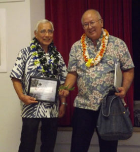 two men in aloha shirts and lei, one holding a framed certificate