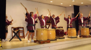 taiko players on stage with arms and sticks raised