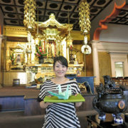 Rev. Yuika Hasebe holds a large origami crane in front of the altar