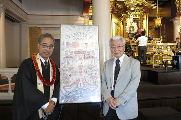 Bishop Matsumoto and Rev. Makino in the hondo next to a framed drawing of the Buddha outdoors