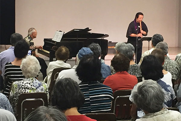 audience watches and listens as Miyoshi Genzan plays the shakuhachi flute and Francis Okano plays piano in the Hawaii Betsuin social hall