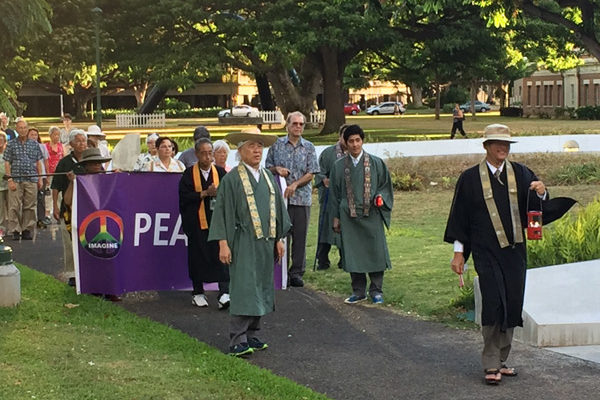 "walkers holding an ""Imagine Peace"" banner led by ministers in robes entering Honolulu civic grounds"