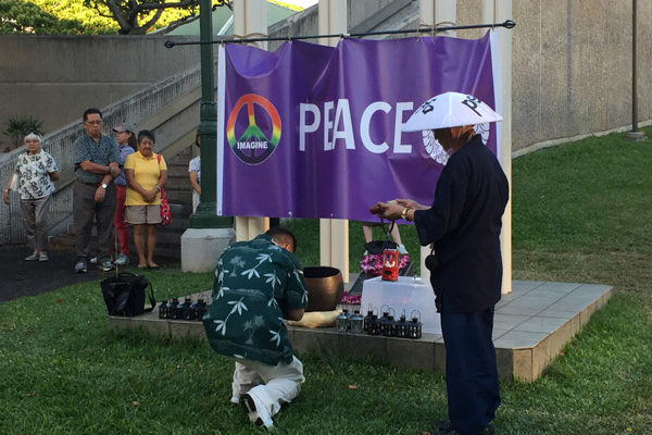 man bows before a peace banner at the Nagasaki Peace Bell