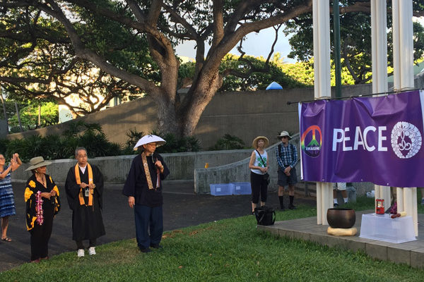 "people encircle the Nagasaki Peace Bell structure, draped with an ""Imagine Peace"" banner"