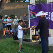 a child receives a mallet to ring the bell at the Nagasaki Peace Bell