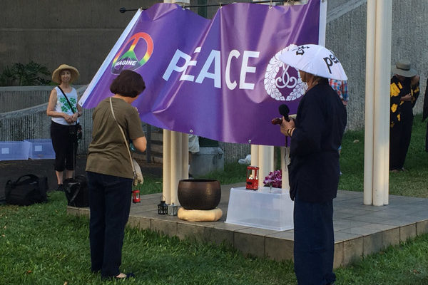 woman bows head before peace banner and candle lantern at Nagasaki Peace Bell