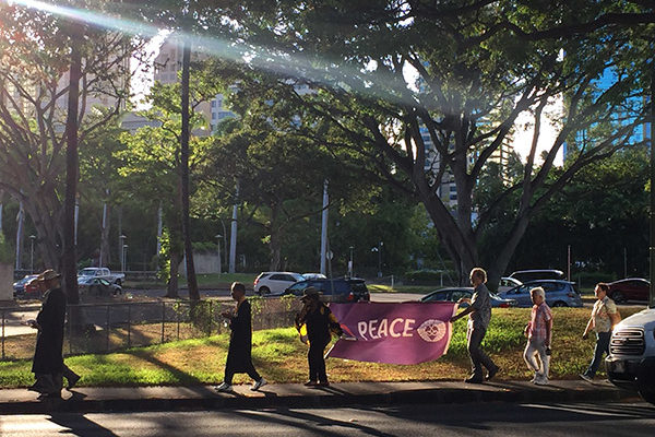 sunlight illuminates the Imagine Peace banner carried by walk participants on Punchbowl St.