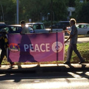 carrying the Imagine Peace banner; silhouette of a minister's robes on backlit banner