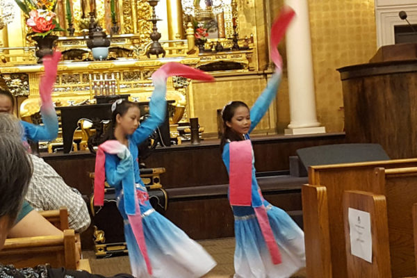dancers in bright dresses with extended sleeves dance in the Betsuin main hall