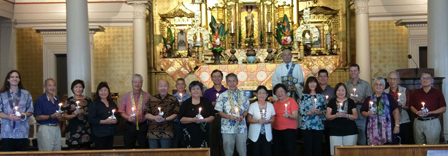 Betsuin board members holding candles facing the pews with the altar in the background